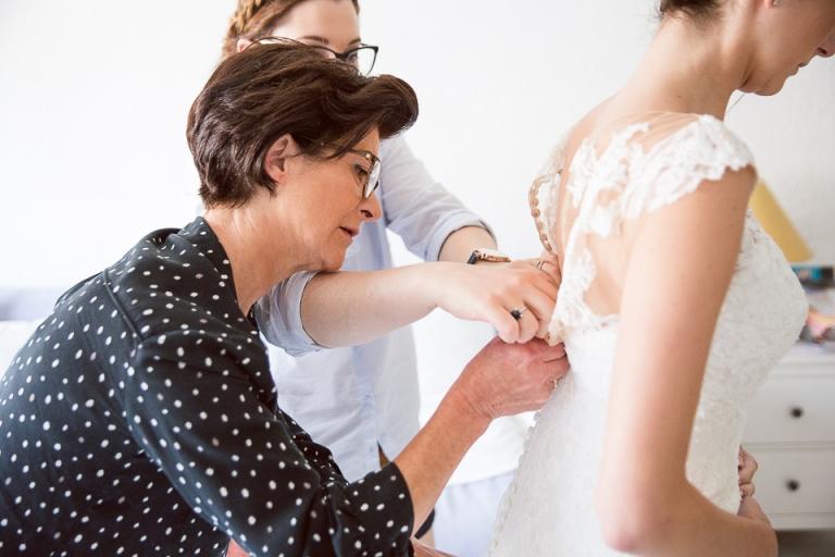 préparation de la mariée, la maman accroche les boutons